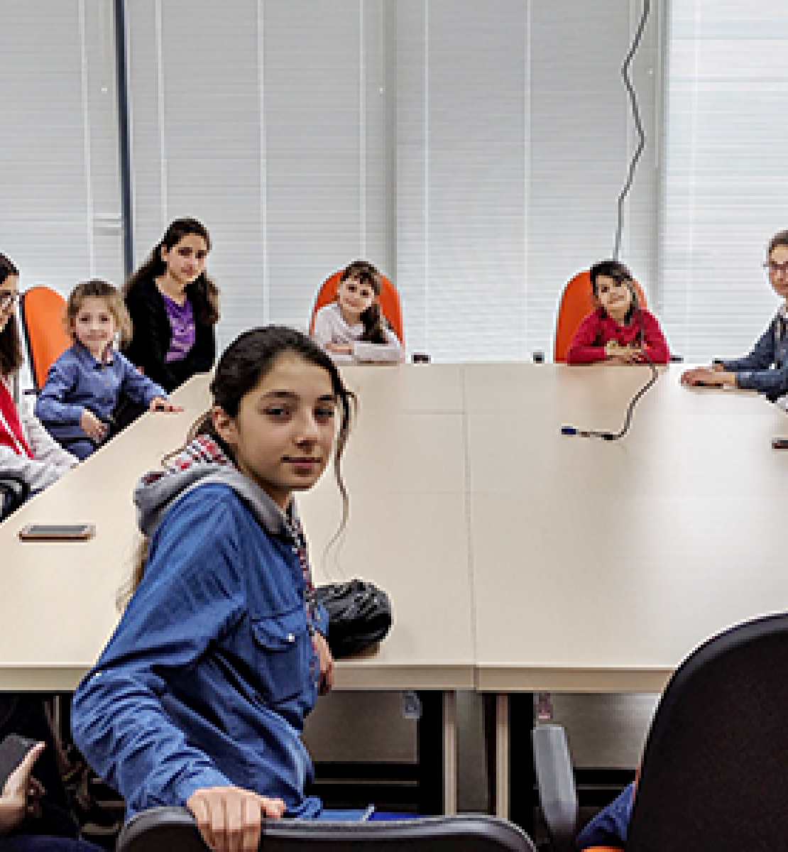 Girls sit around a conference room table