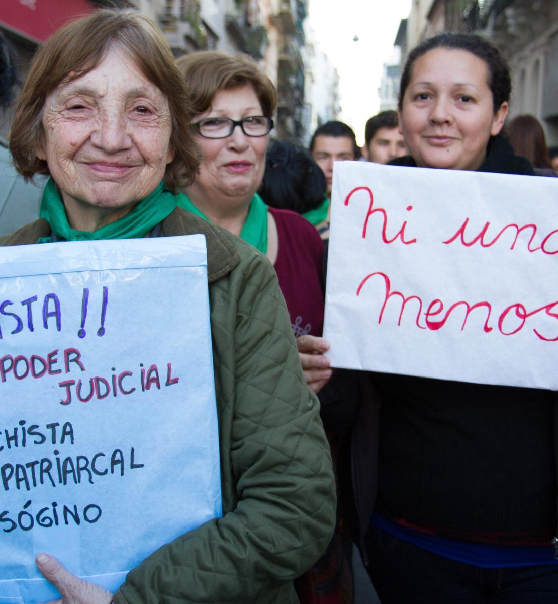 Deux manifestantes brandissent des pancartes en souriant à la caméra.