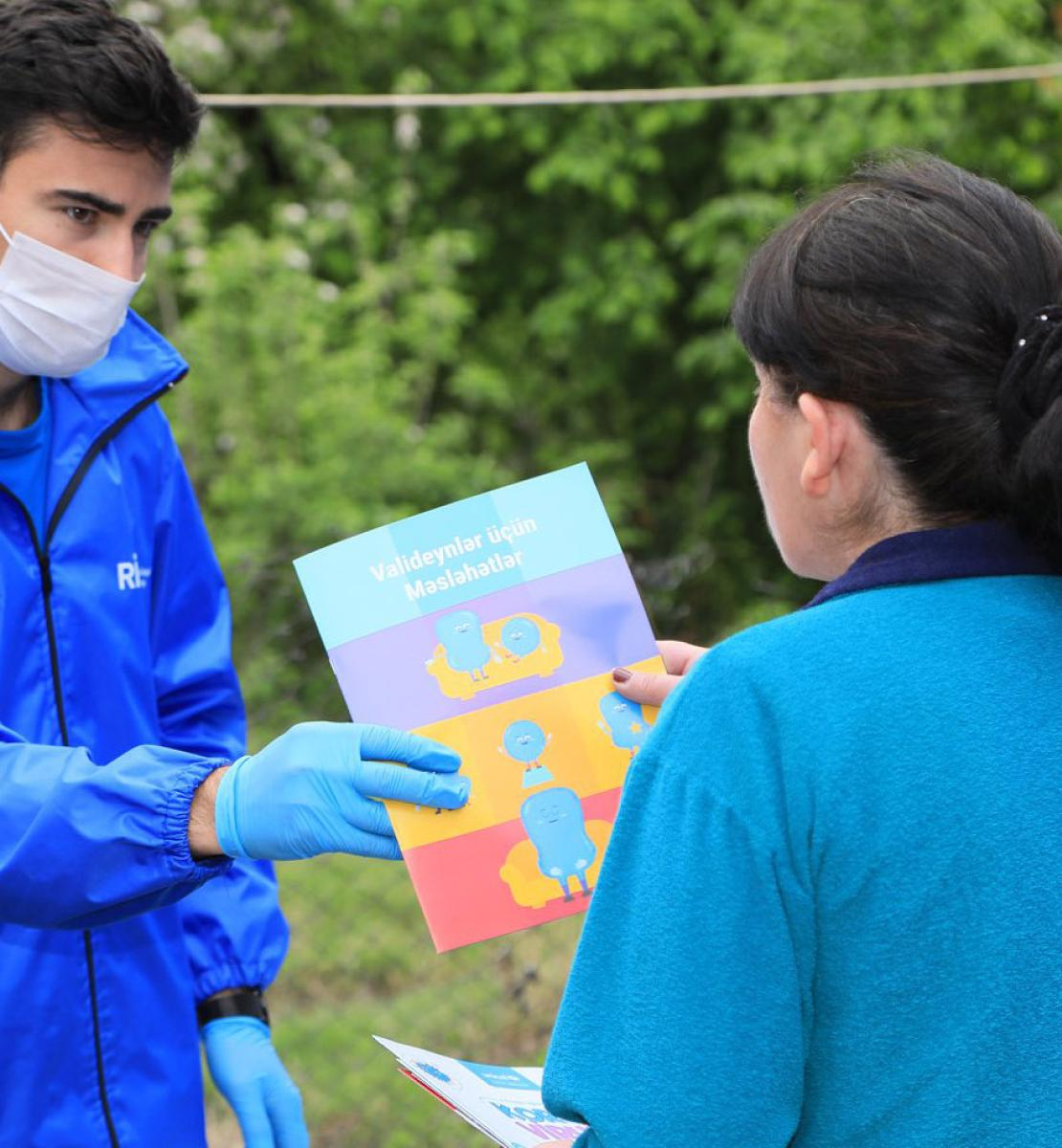 Voluntarios dedicados proporcionan material de concienciación sobre la COVID-19 para ayudar a la comunidad a prevenir la propagación del virus.