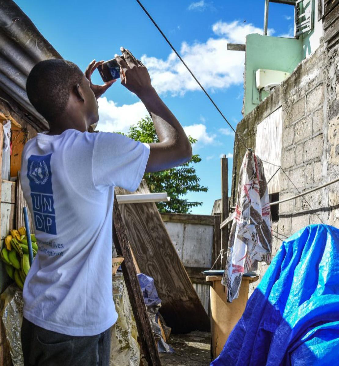Dans une ruelle exigüe jonchée d'objets en tous genres, un jeune homme vêtu d'un t-shirt au dos duquel on peut voir le logo du PNUD prend en photo le mur qui se trouve en face de lui à l'aide de son téléphone mobile.