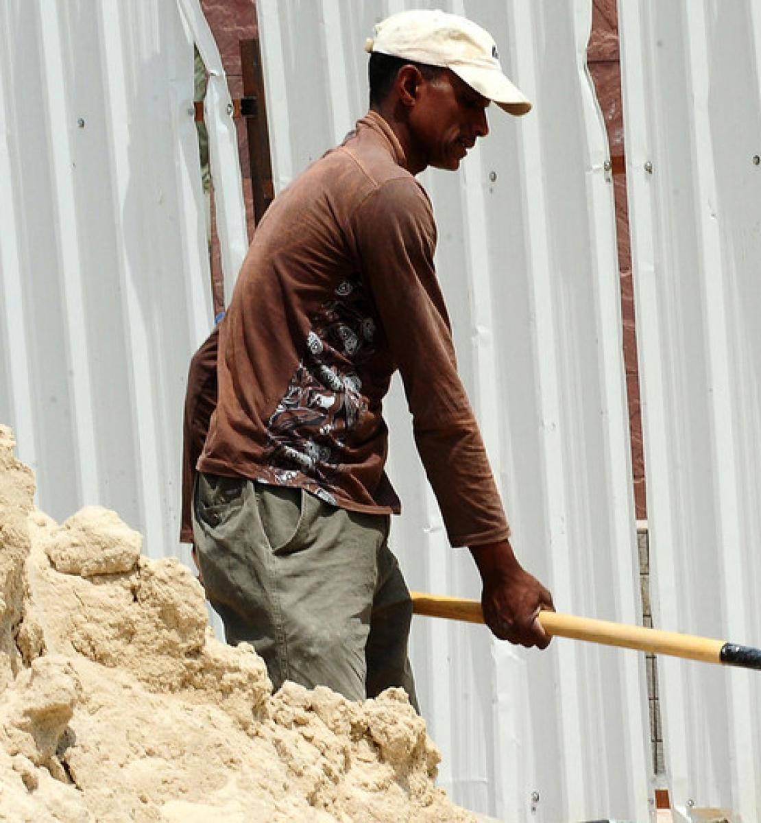 Un ouvrier déblaie un terrain de sable sur un chantier de construction.