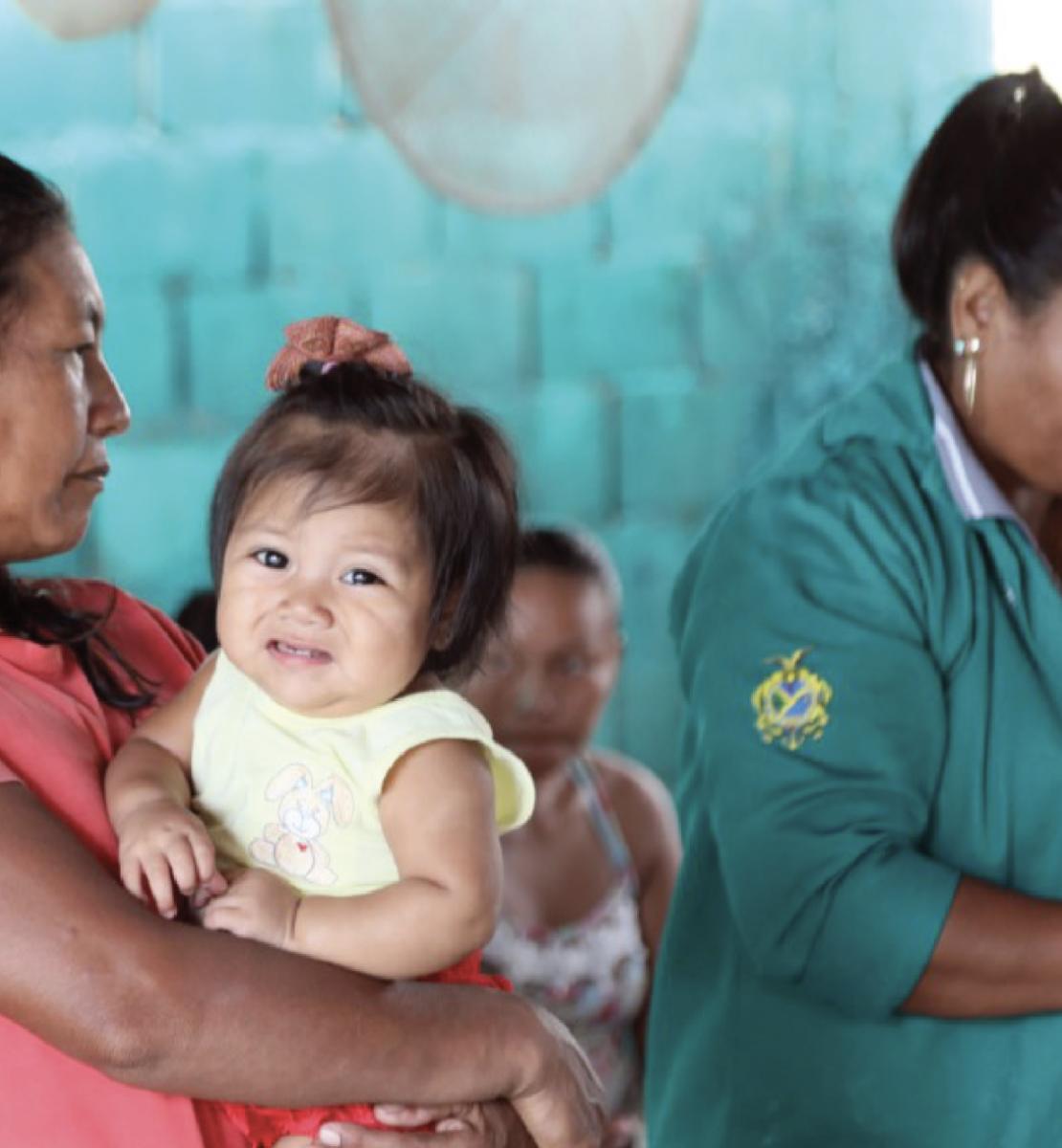 Une femme autochtone tient une petite fille dans les bras, à gauche de l'image, en attendant d'être soignée par une agente de santé dont on voit qu'elle prépare son matériel à droite de l'image. La femme autochtone regarde en direction de l'agente de santé tandis que sa fille regarde la caméra le visage grimaçant.