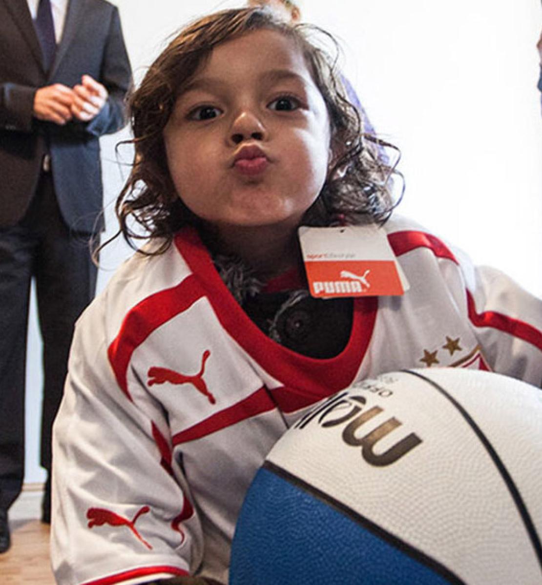 Un niño vestido con un chándal deportivo, sostiene una pelota de baloncesto con ambos brazos y mira a la cámara, haciendo el gesto de estar mandando un beso, con los labios fruncidos.