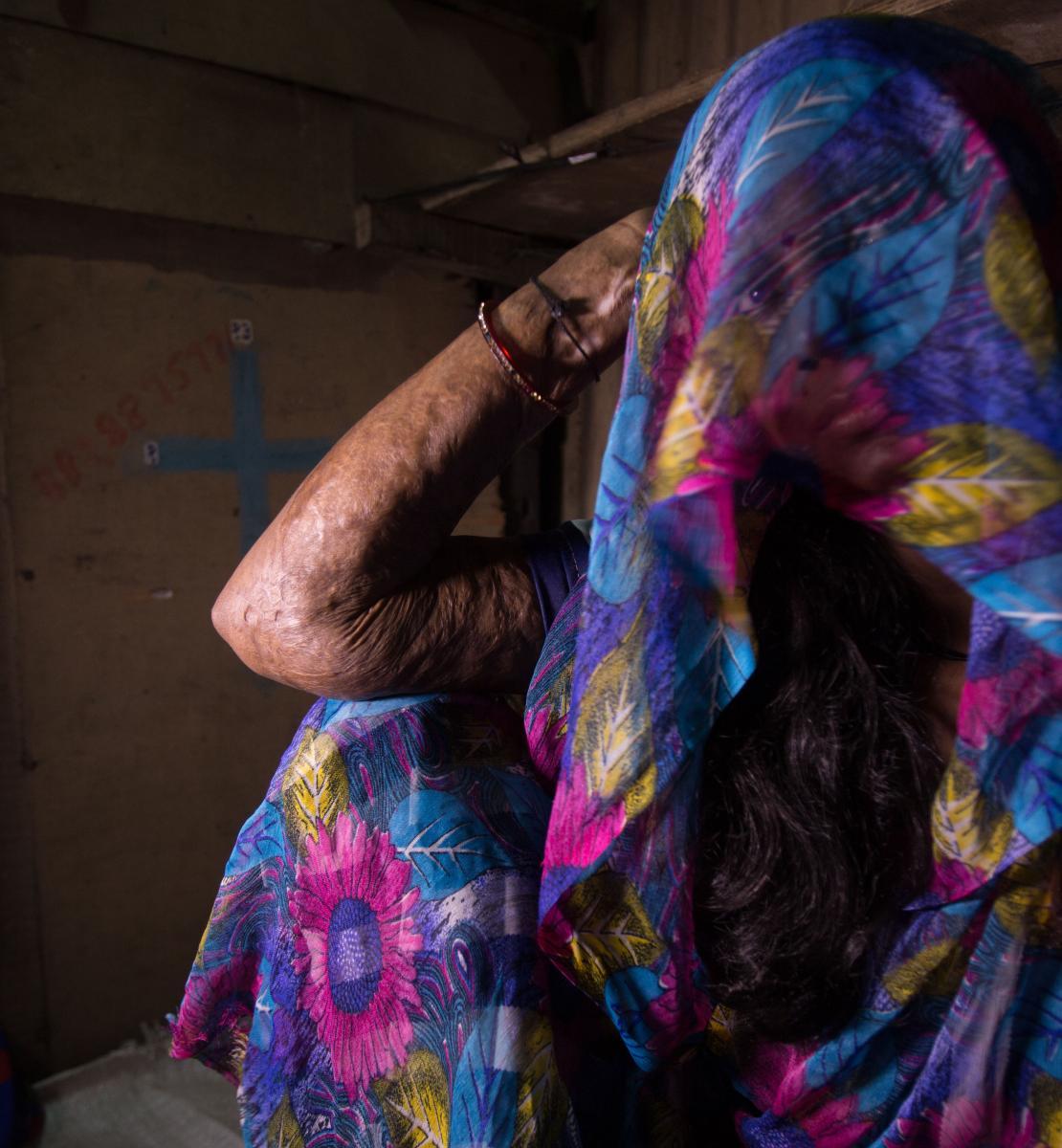 一个女人坐在地板上,看着镜头,她头上的衣服遮住了脸。
