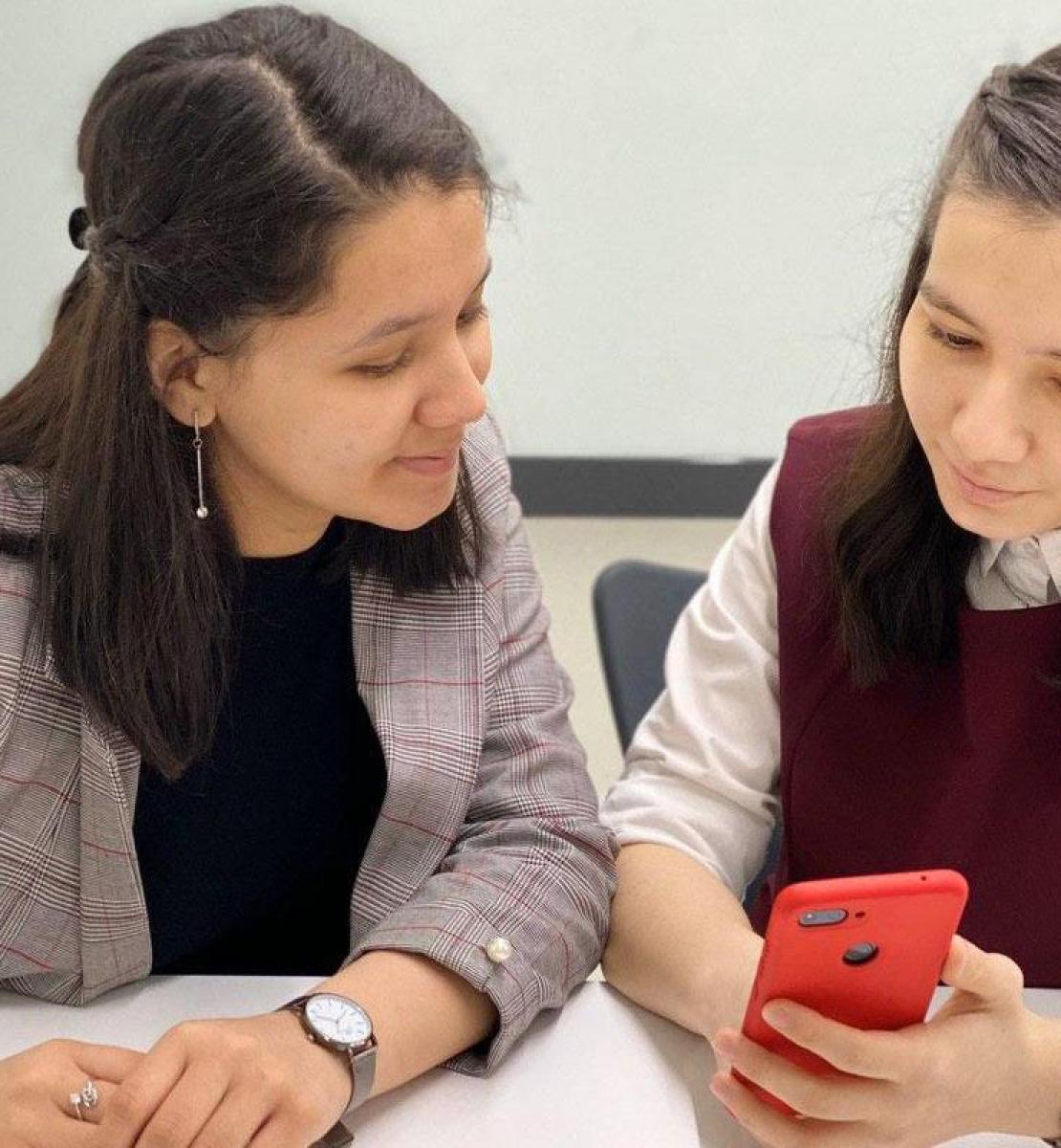 Девочка учится пользоваться программой на мобильном телефоне вместе со своим учителем.