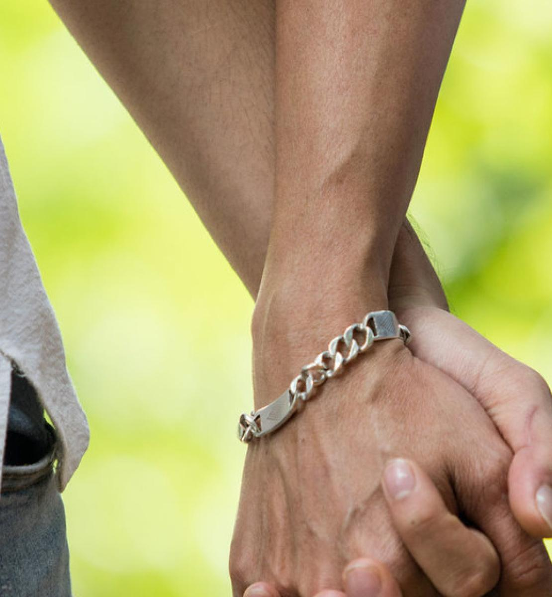Close up image of two people, wearing jeans and light dress shirts, holding hands.
