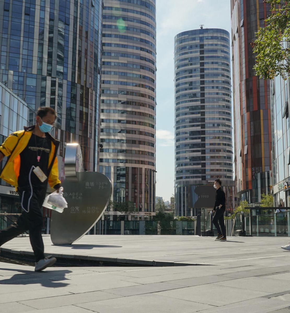 在中国北京,一名戴着口罩的送餐员跑着送餐。