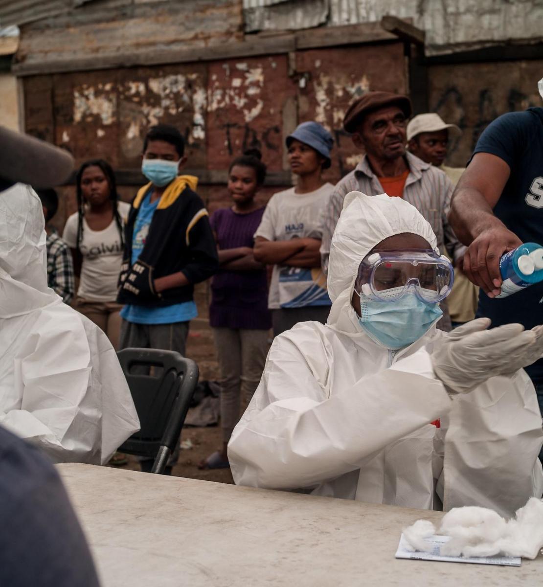 图片显示,人们在全身穿着防护装备的医护人员桌子后等待。站在医护人员身后的一名男子将消毒液倒在其中一名医护人员的手上,而一名男子则坐在医护人员前面等待。