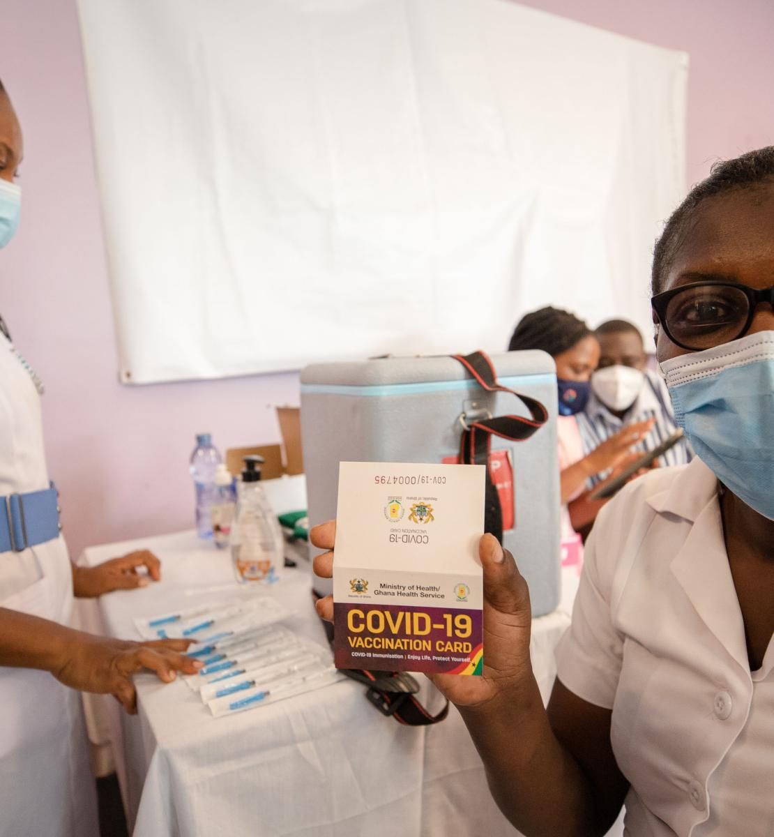 A healthcare professional at a vaccination site proudly holds up a COVID-19 vaccination card that verifies she received the vaccine.