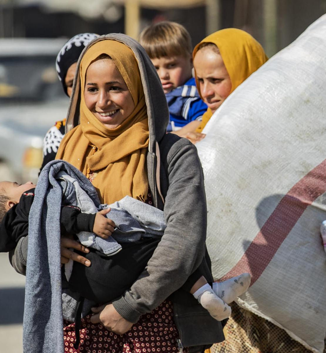 A woman smiles as she carries a sleeping child. Another woman walks behind her as she carries a large bag.