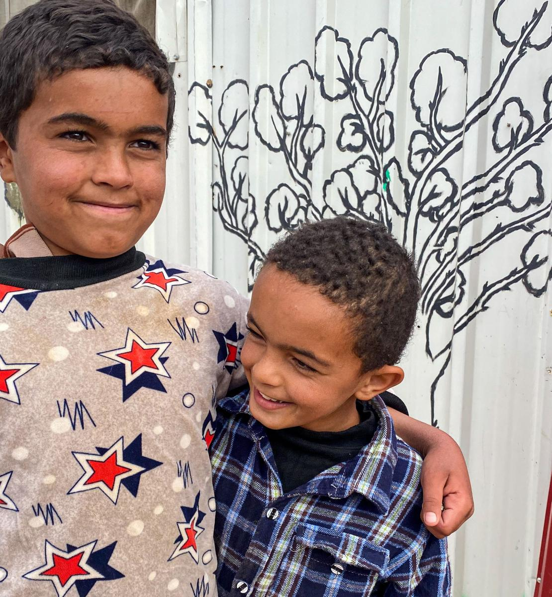 Two small boys with arms around each other smile happily as they stand outside by a wall that has a mural painting.