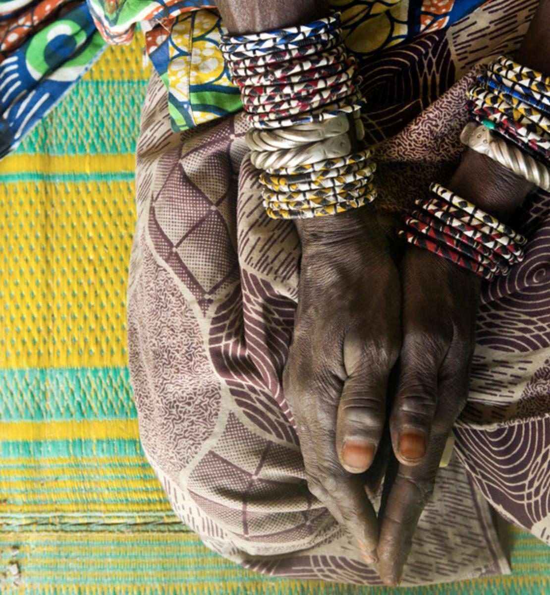 Gros plan sur les mains d'une femme portant plusieurs bracelets et agenouillée sur une étoffe aux couleurs vives.