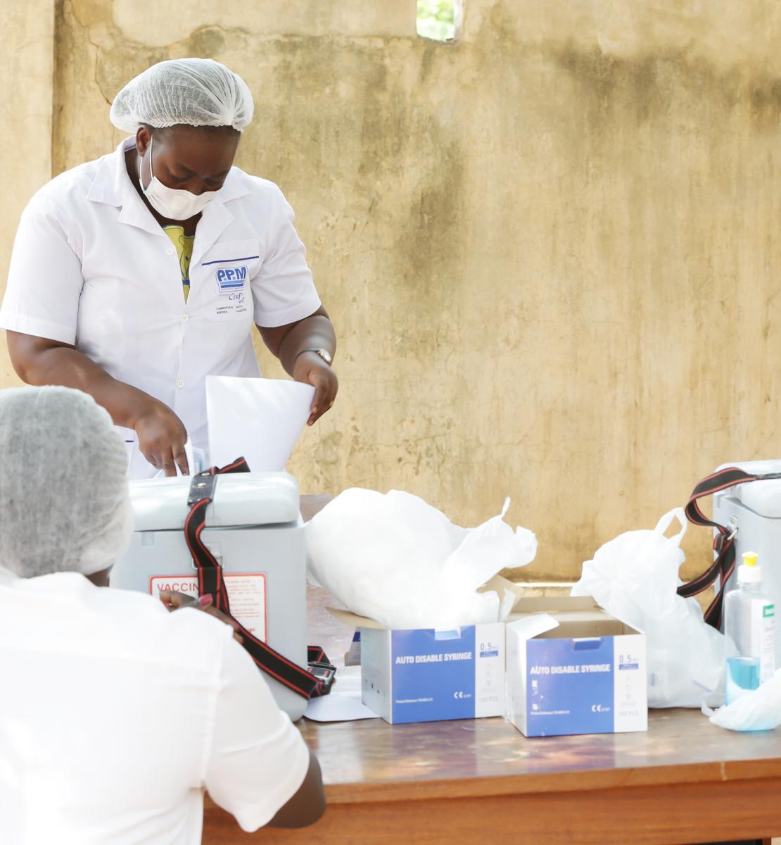 Quatre hommes et femmes portant chacun(e) un masque de protection respiratoire préparent le matériel nécessaire à l'administration de vaccins anti-COVID-19.