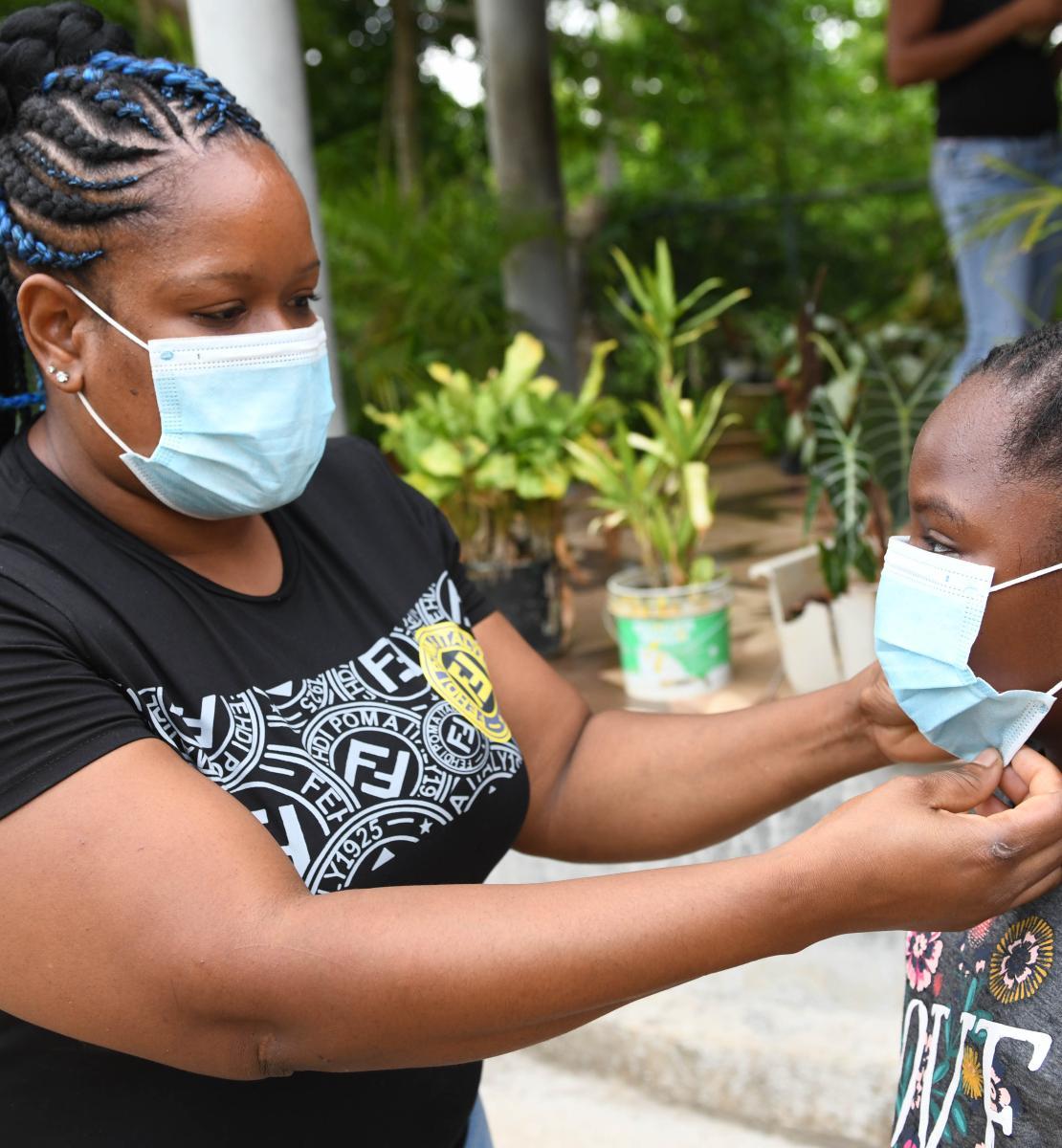 Dans une cour extérieure bordée d'arbustes, une femme ajuste le masque de protection de sa fille, une élève de l'école primaire de Little Bay. Little Bay est une commune principalement composée de pêcheurs située à Westmoreland, à l'extrémité ouest de l'île de la Jamaïque.