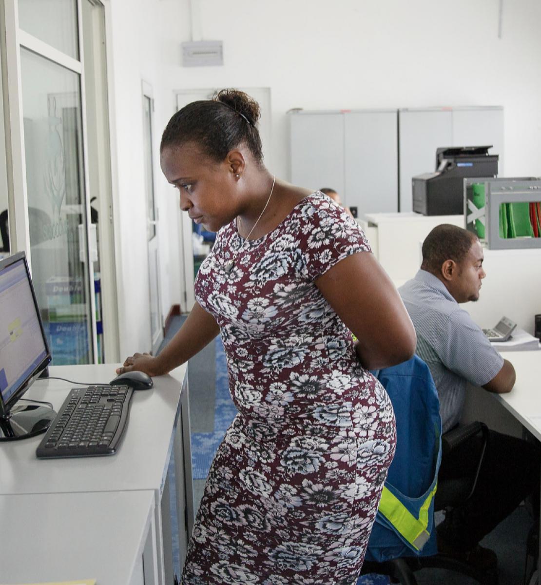 Женщина в платье работает за компьютером, а мужчина рядом с ней работает, сидя за своим столом.