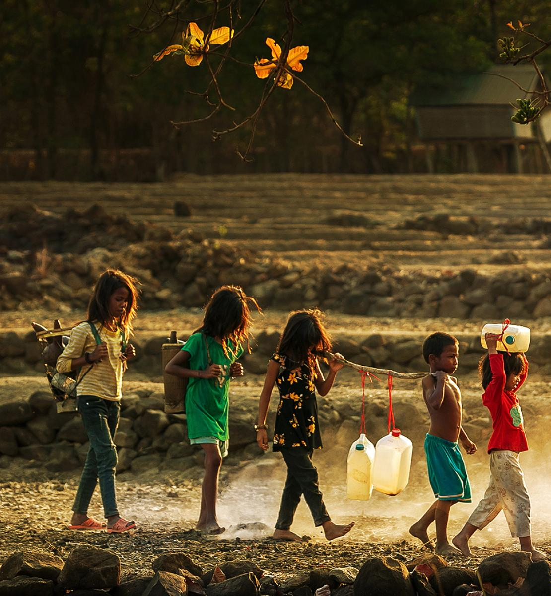 Little children walk in a line as they all hold a large stick holding jugs of water.