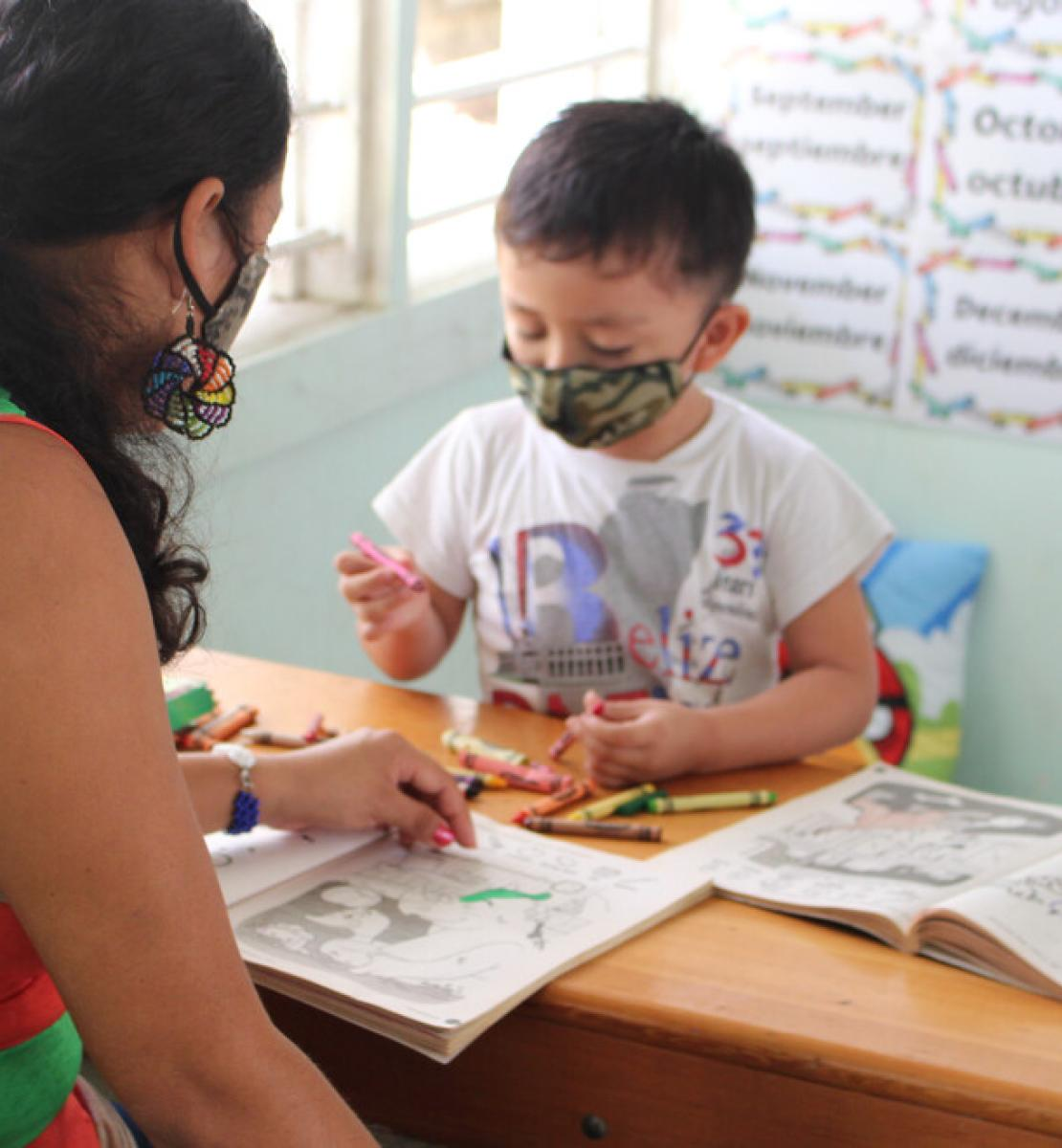 A woman and a child in face masks look over coloring books on a wooden table.