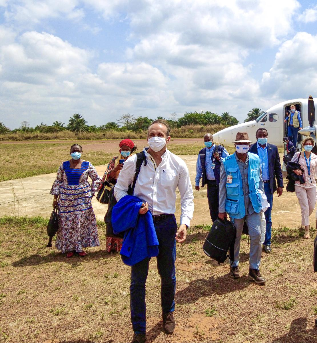 Several people in face masks, holding bags, and jackets, deplane in a field on a sunny day.