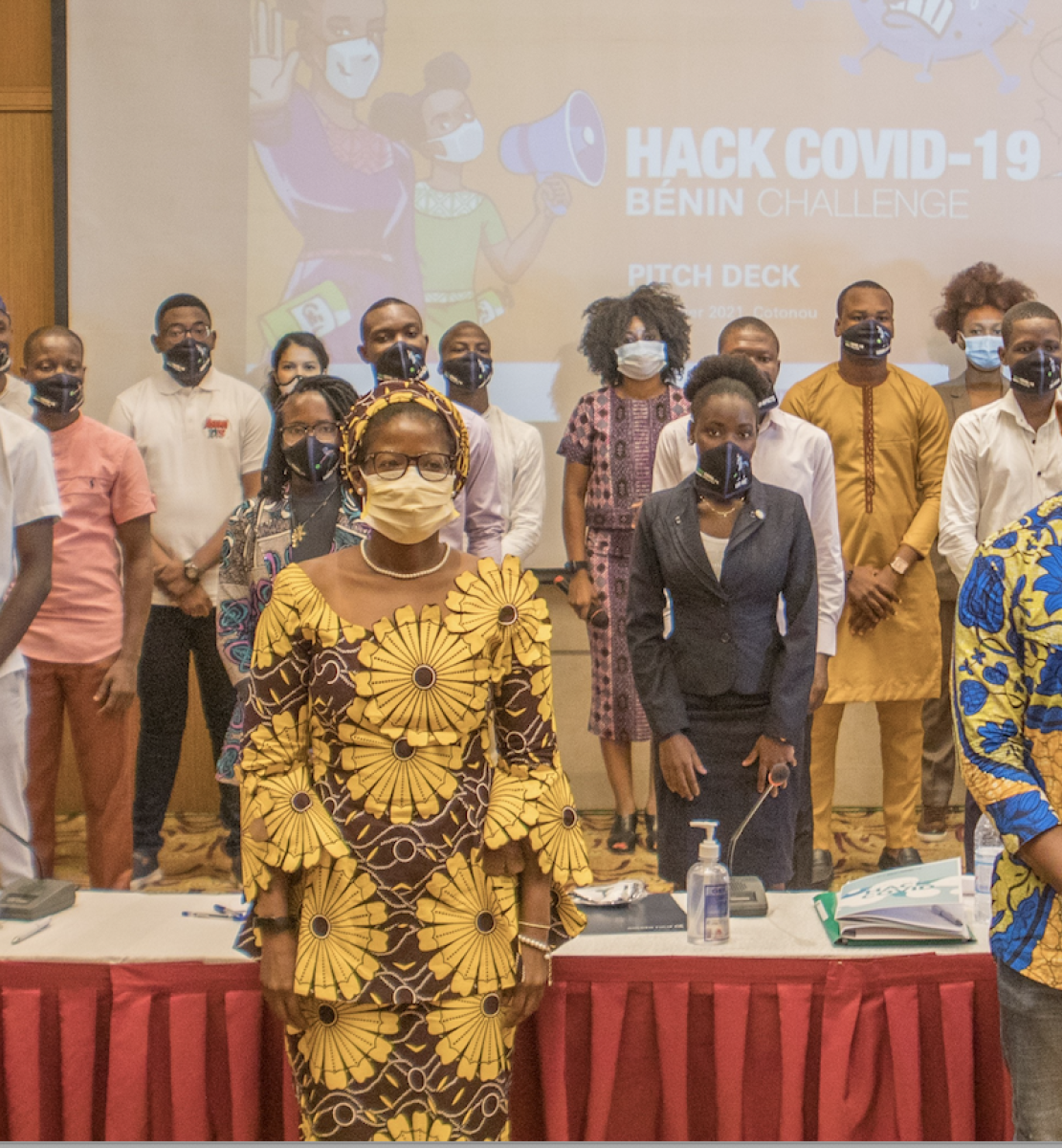 """A large group of people in face masks stand facing the camera in front of projector displaying the words """"Hack COVID-19."""""""