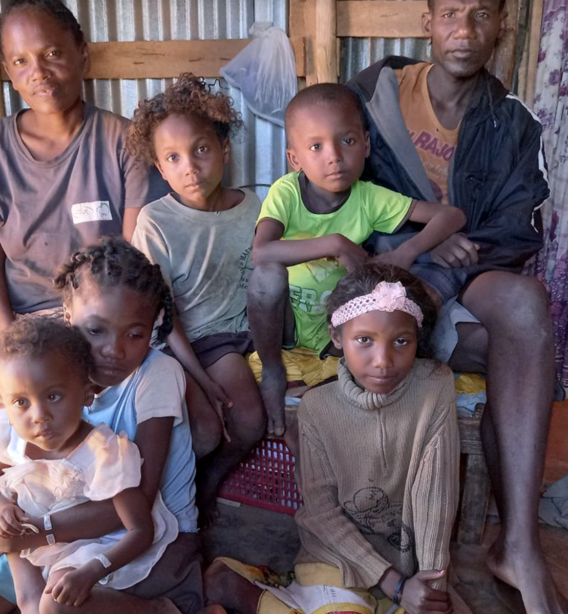 Un père, une mère et leurs enfants sont assis côte à côte dans une des pièces de leur maison, face à la caméra.