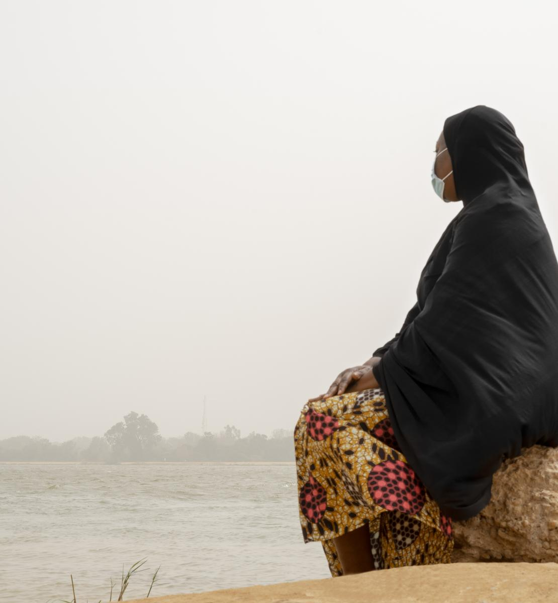 A woman sits on a rock looking out into the distance over a body of water.