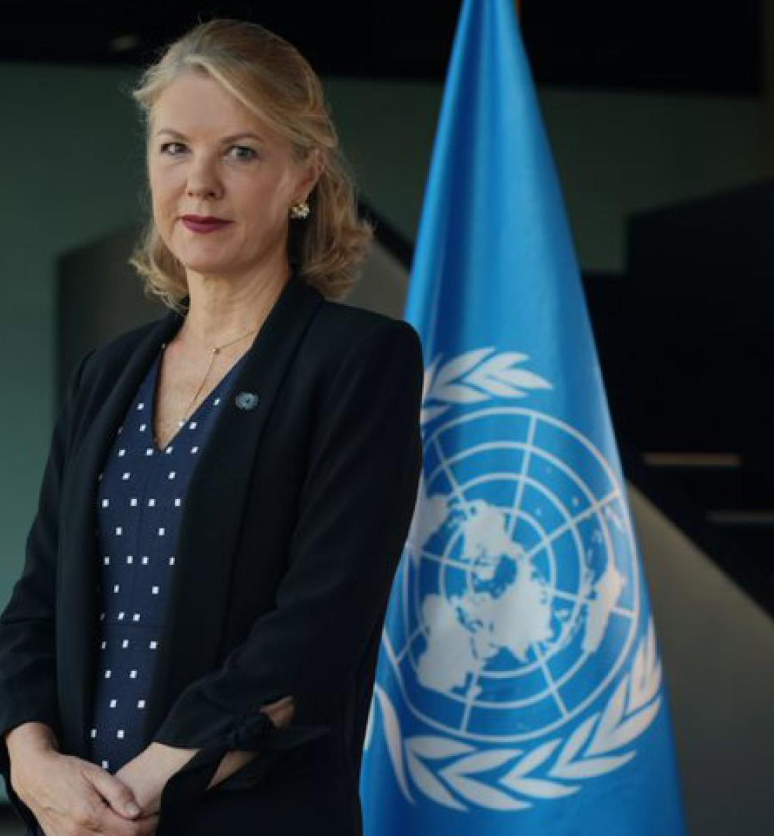 A woman in a blue dress and a black jacket stands in front of the United Nations flag.