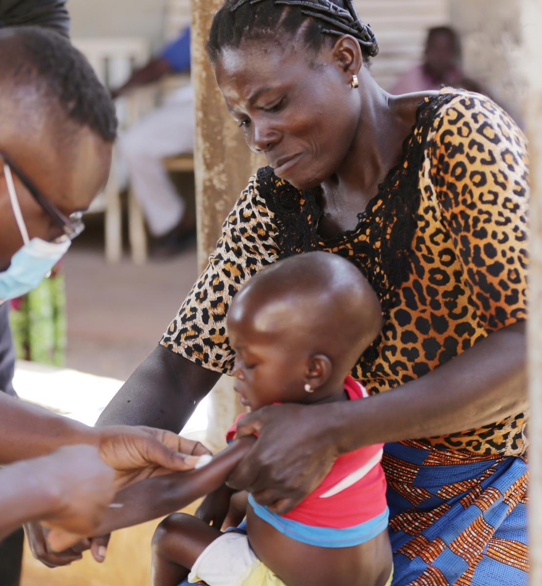 Ребенок, сидящий на руках у женщины, получает инъекцию в руку от мужчины в желтой футболке