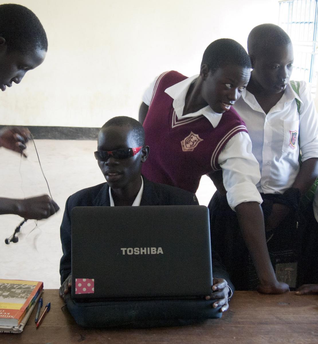 Denis Komakech, un élève de 17 ans atteint de cécité, installe son ordinateur avec ses camarades de classe au lycée de Gulu, dans le nord de l'Ouganda.