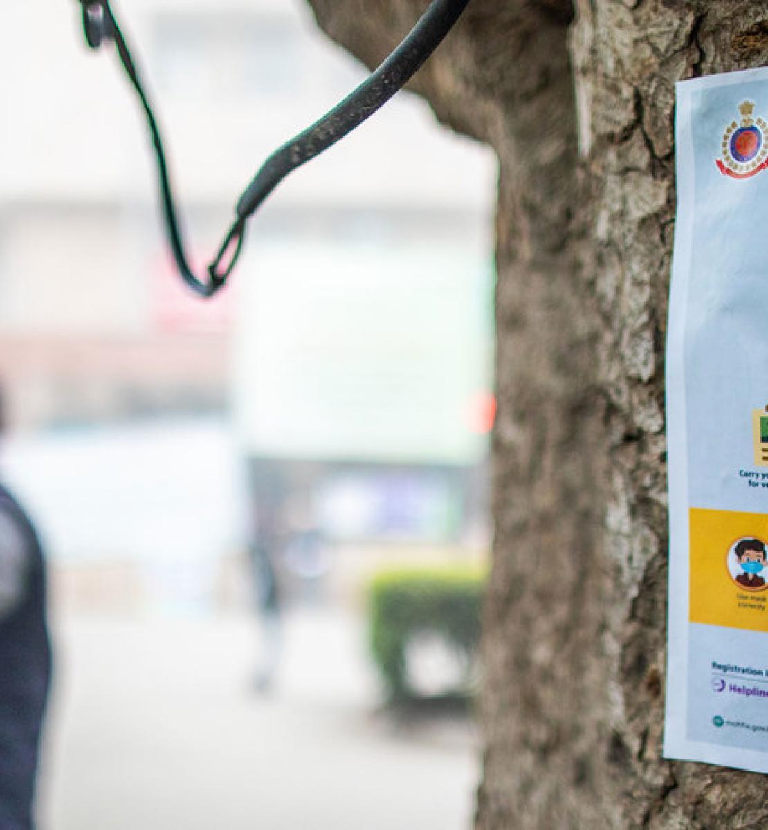Une affiche a été accrochée à un tronc d'arbre. On peut y lire, en anglais « COVID-19 Vaccine is safe ! », ce qui signifie « Le vaccin anti-COVID-19 est sûr ». En arrière-plan, un homme portant une casquette et un masque de protection lève le bras, comme pour indiquer que la voie est libre.