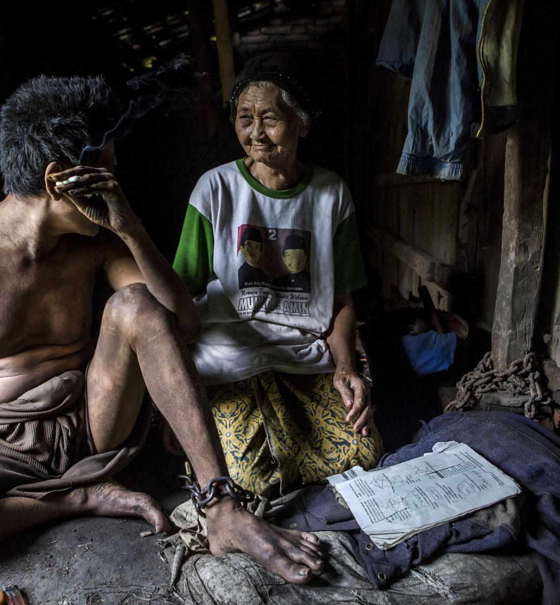امرأة ورجل ينظران إلى بعضهما البعض أثناء جلوسهما على الأرض. الرجل مقيّد حول ساقيه ويدخّن سيجارة.