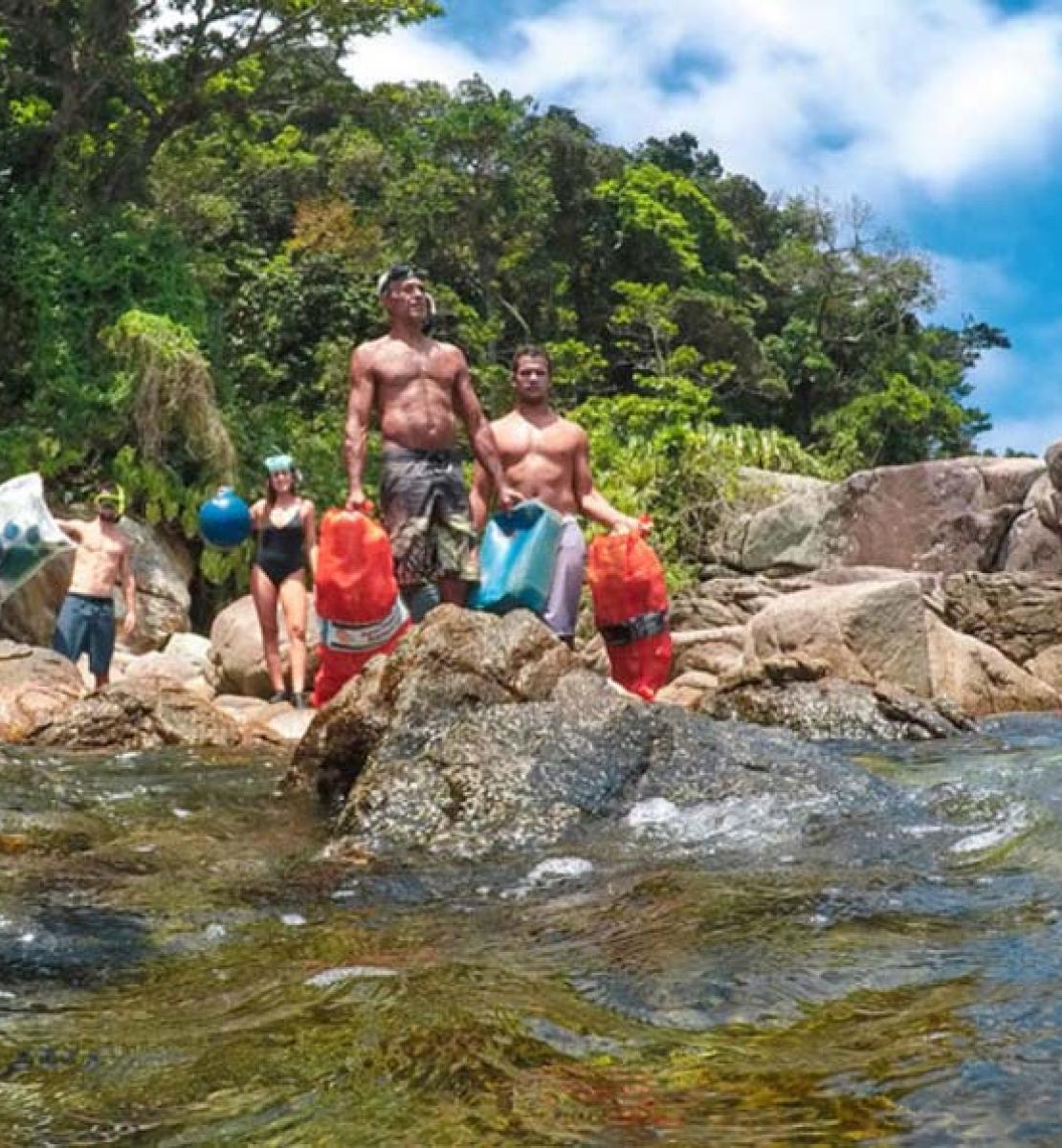Cuatro personas, en traje de baño y con equipamiento para realizar una limpieza, se paran sobre rocas cerca del océano.