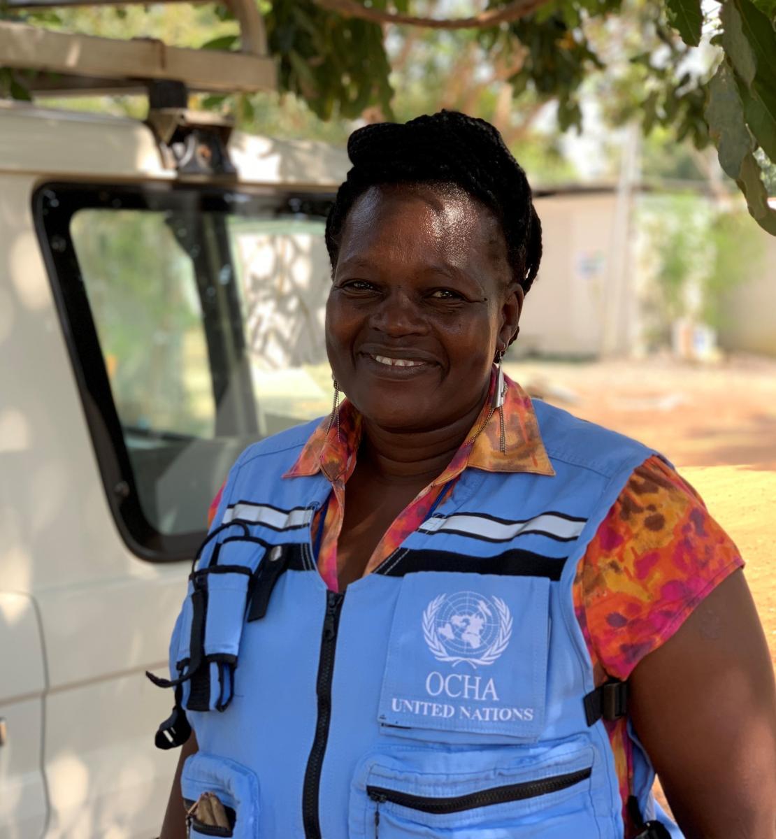 一名身穿蓝色联合国夹克的妇女对着镜头微笑。