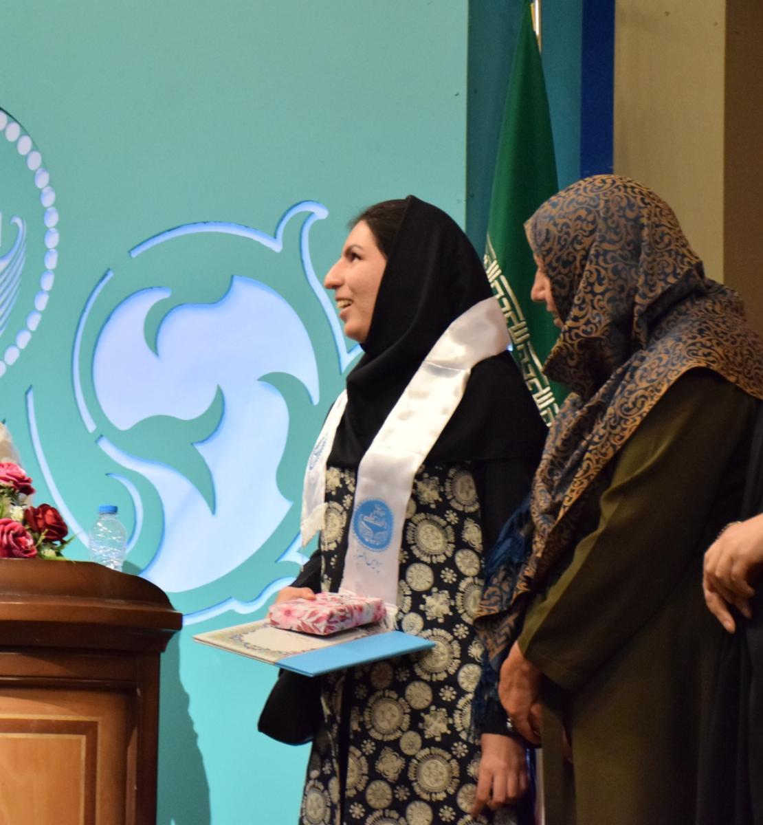 Три человека стоят на сцене возле подиума и зеленого логотипа.