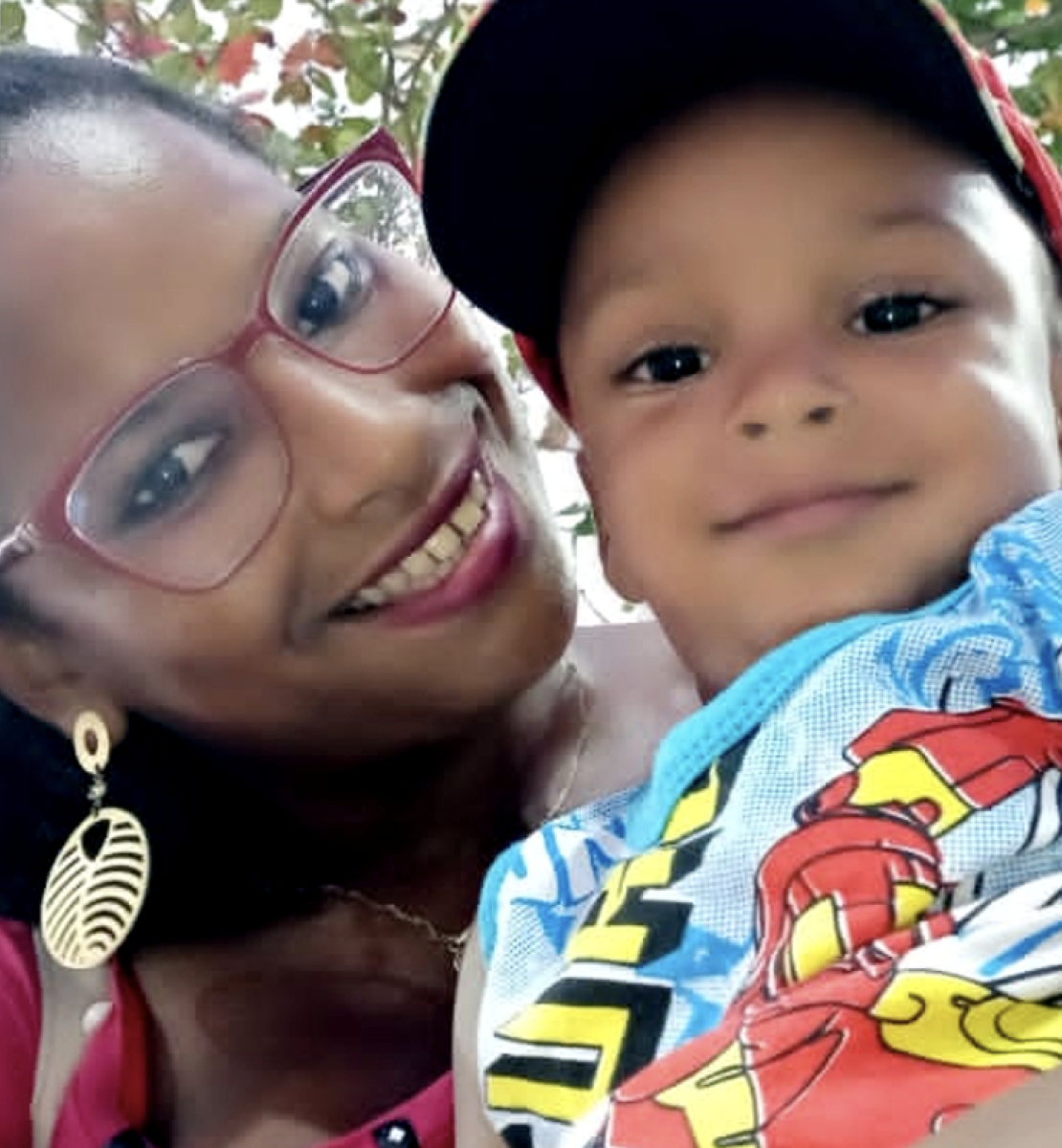 A woman in a pink shirt and glasses smiles at the camera with a child in a tank top and ared hat.