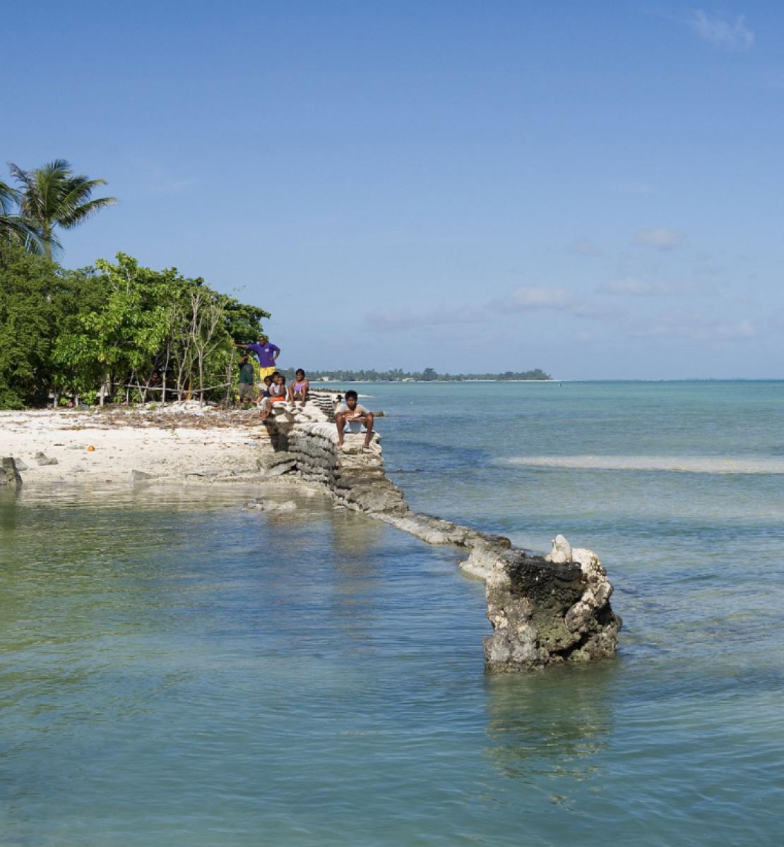 Изображение океана и нескольких людей, стоящих на острове в солнечный день.