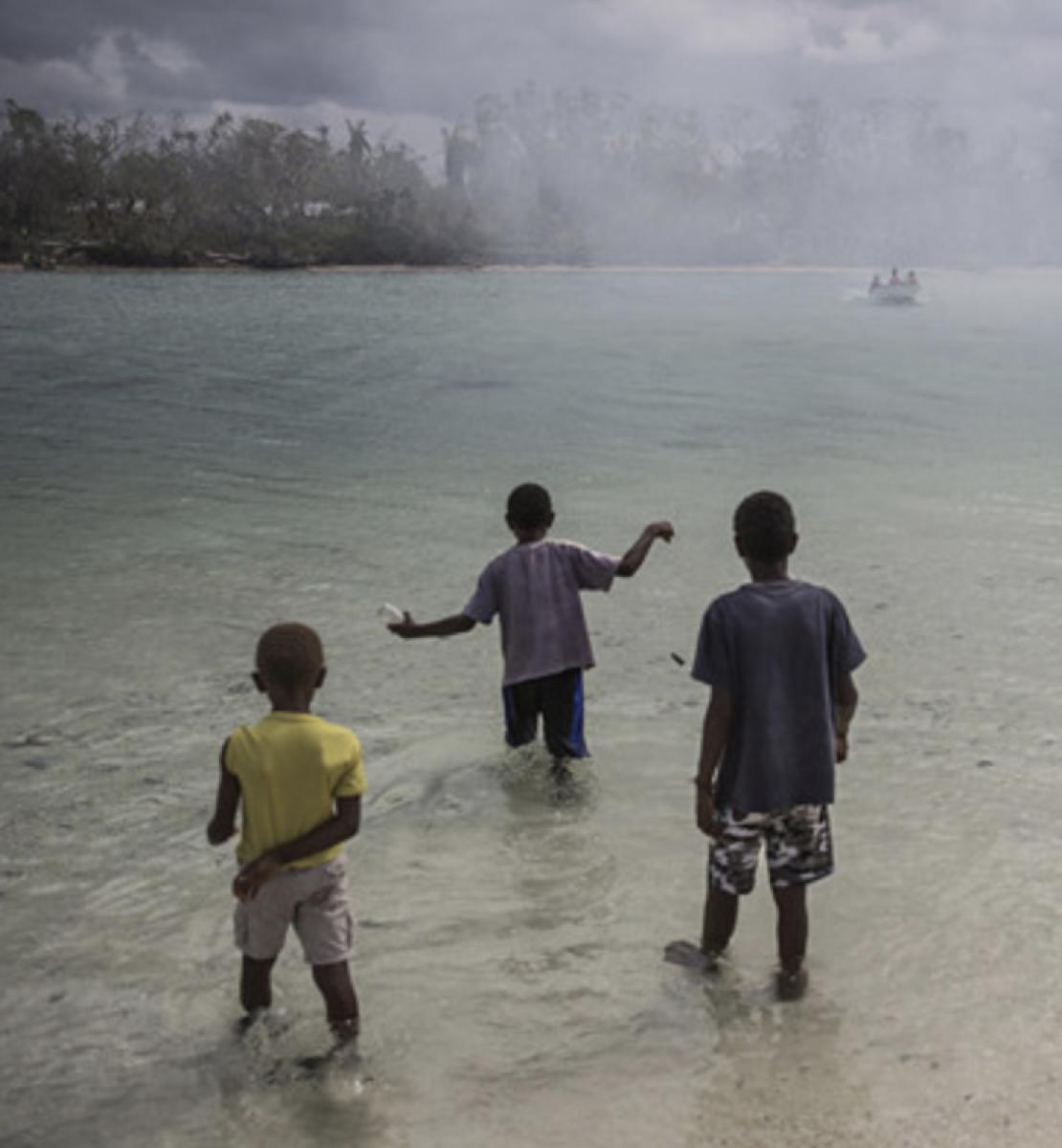 Трое детей стоят в водоеме, наблюдая за проплывающей рядом лодкой.