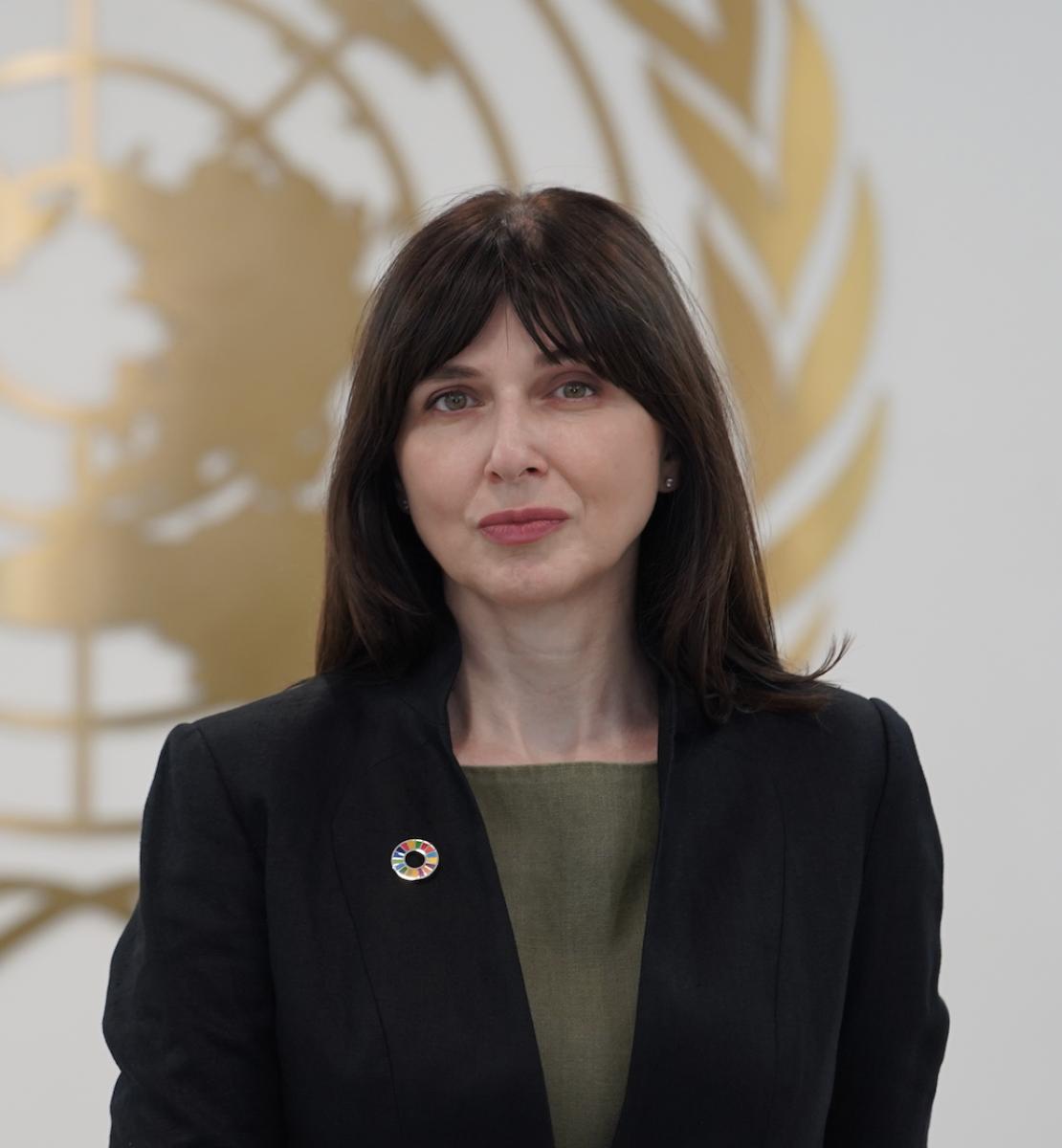 一名妇女站在联合国标志前,身穿黑色夹克和绿色衬衫,直视镜头。