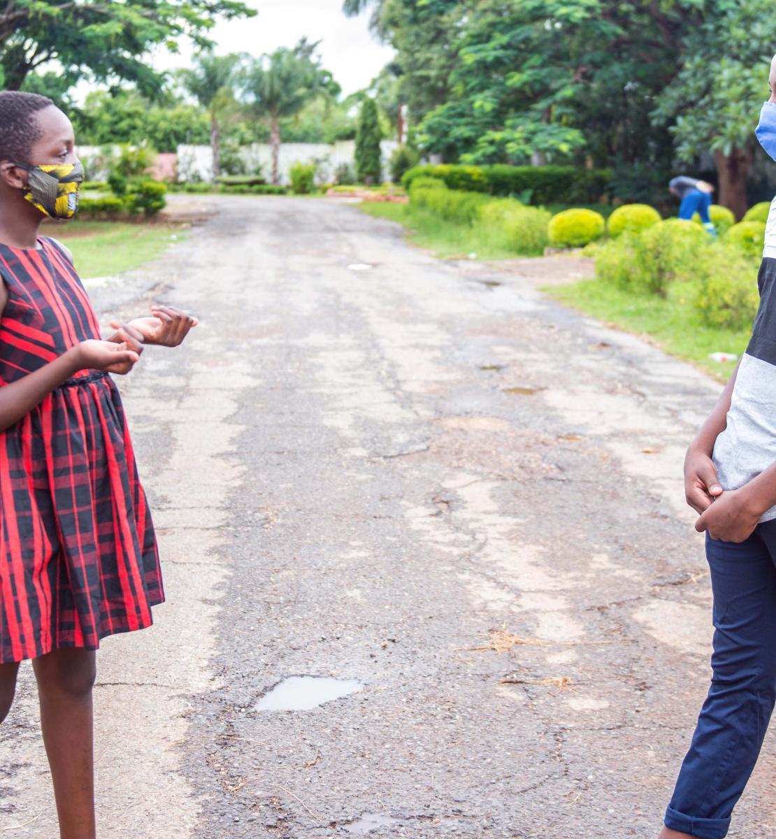 Una niña y un niño adolescentes con mascarillas demuestran su distanciamiento social al separarse mientras conversan, en medio de una carretera de tierra en una zona verde, en Lusaka, Zambia.