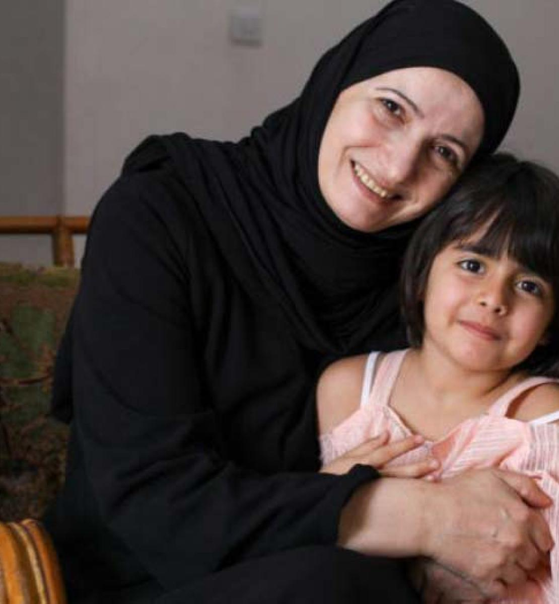 Ghada smiles cheerfully as the camera as she proudly embraces her youngest daughter, who is also smiling at the camera.