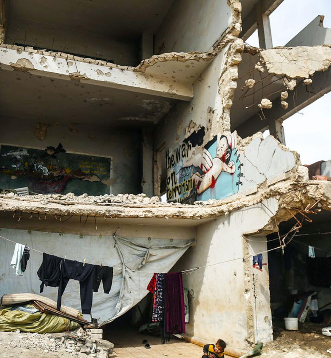 Женщина в синем платье и несколько детей стоят в наполовину разрушенного здания.