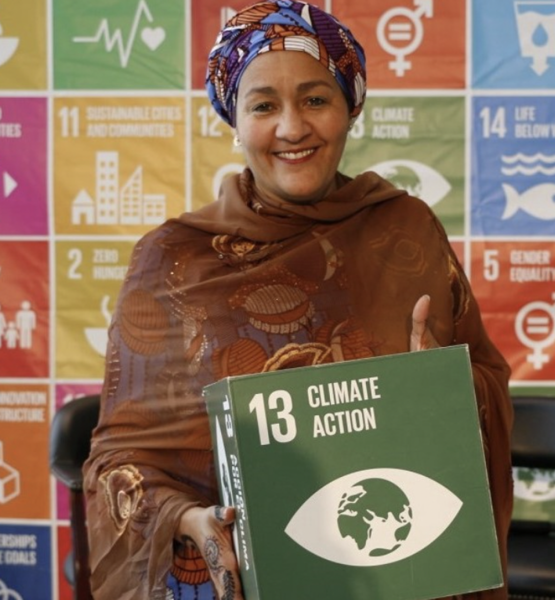 Amina Mohammed, the UN Deputy Secretary General smiles at the camera while holding a green box displaying the words Climate Action in English.