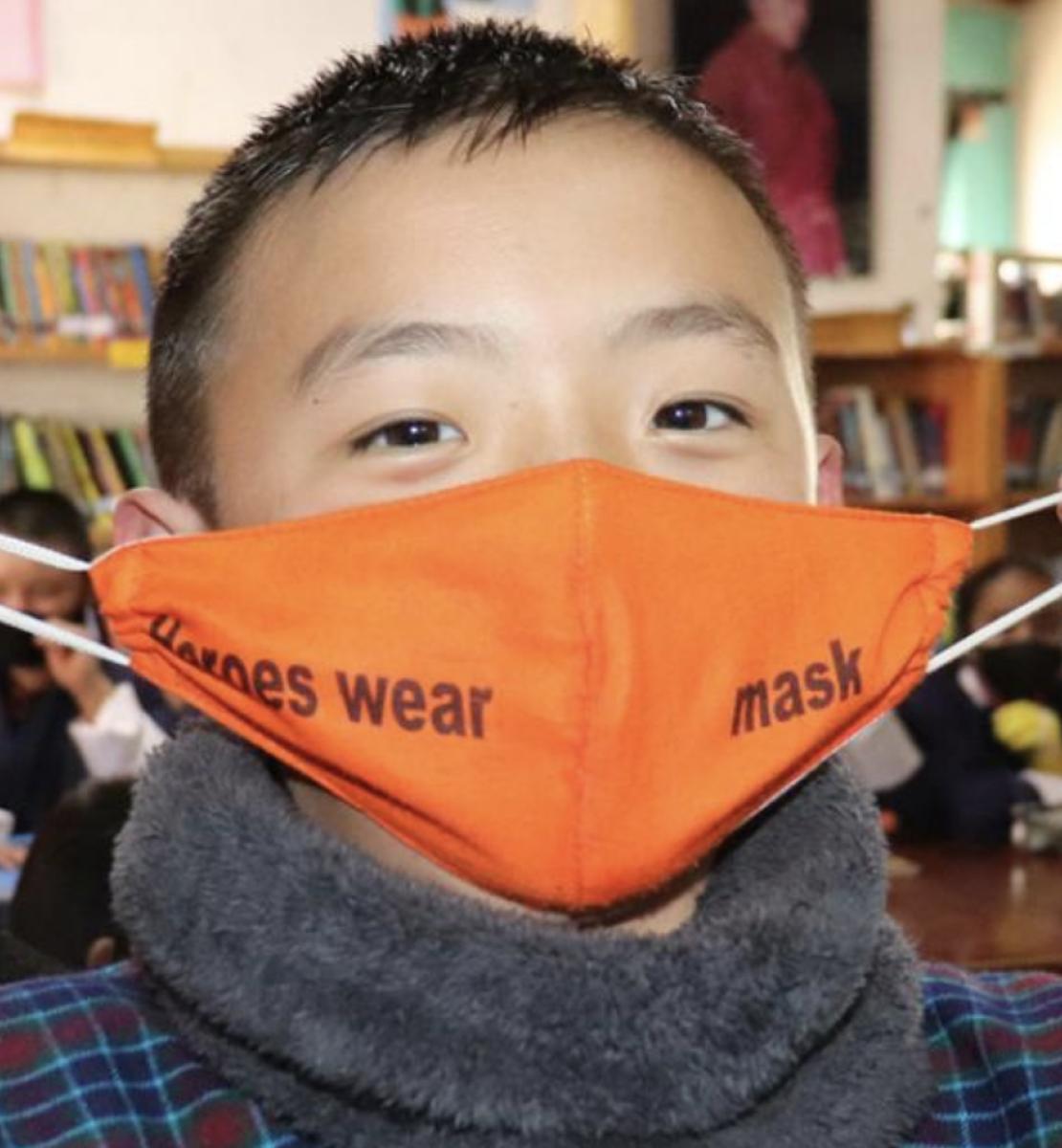 Un jeune garçon enfile un masque de protection orange en regardant en direction de la caméra.