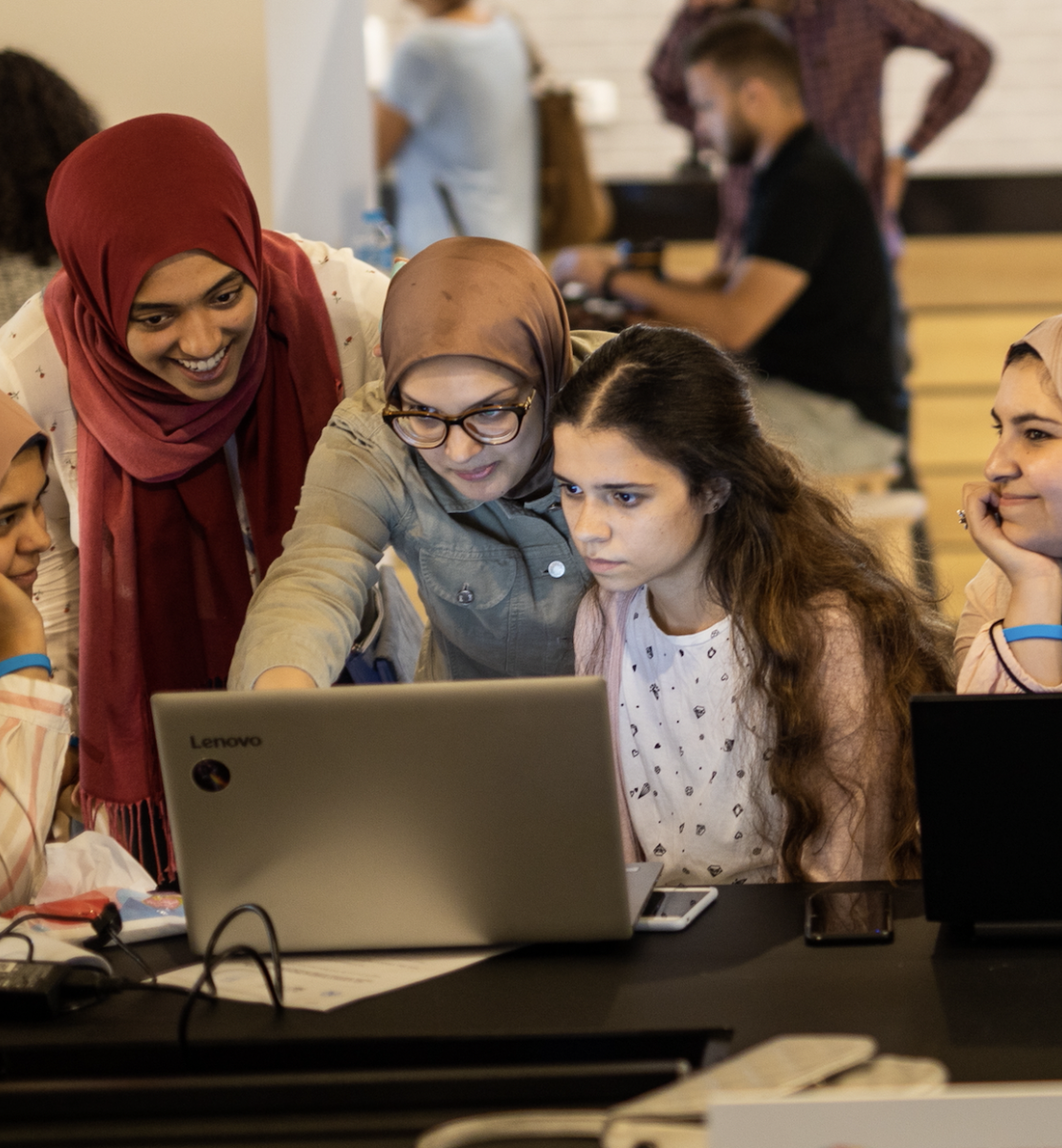 Пятеро девушек вместе смотрят на экран одного из ноутбуков в комнате с несколькими другими людьми.