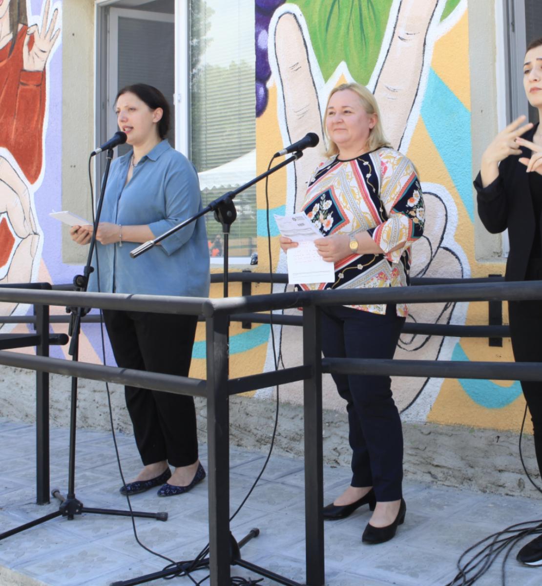 三名妇女站在一栋装饰着多种颜色的建筑物前。一头的黑衣女子正在将讲话内容翻译成手语。