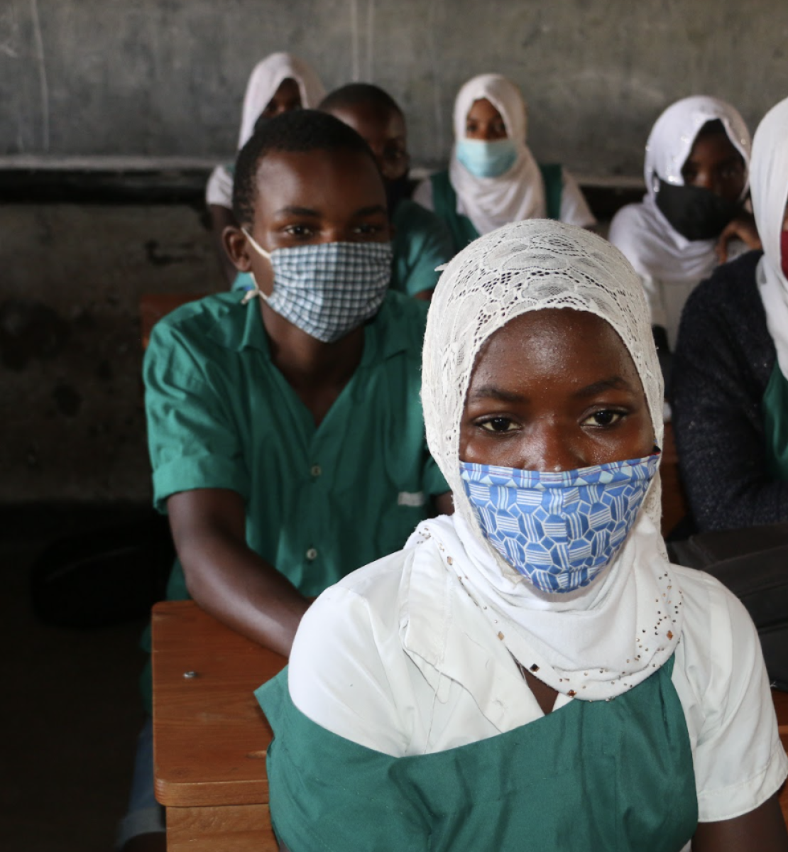 A group of children in school uniforms and masks sit in a classroom facing forward.