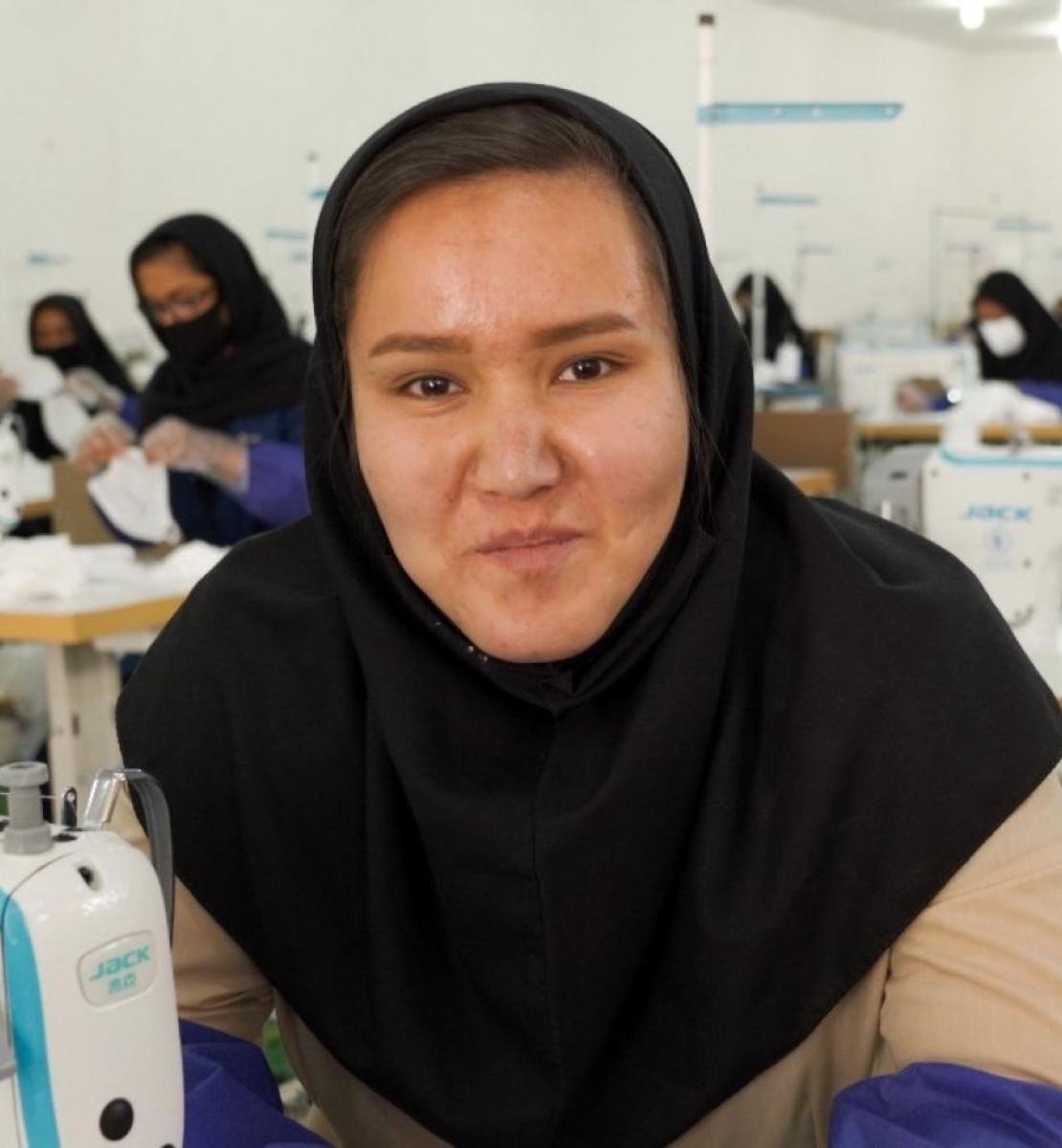 Una mujer joven mira directamente a la cámara en una sala llena de mujeres que trabajan con máquinas de coser.
