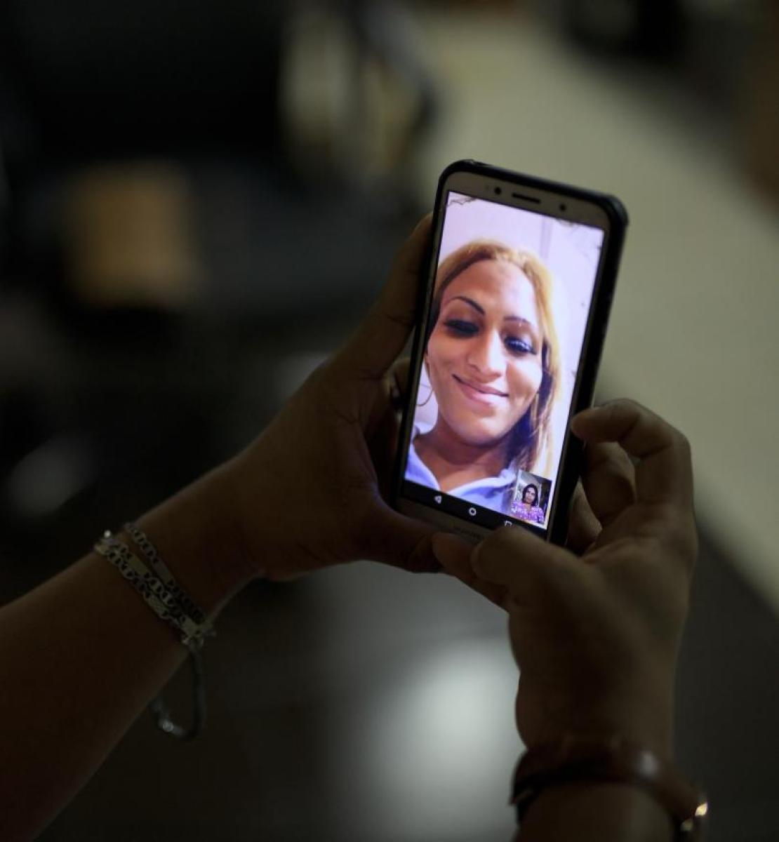 Una imagen de la mano de una persona sosteniendo un teléfono móvil, en el cual aparece la imagen de otra persona, en vio y directo.
