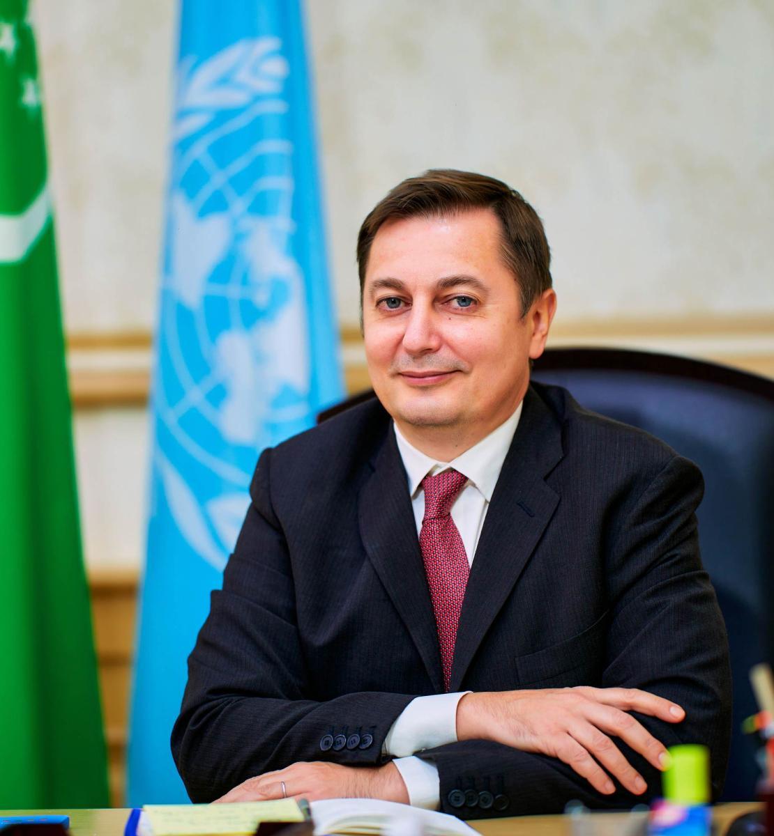 一名身着西装的男子拿着土库曼斯坦和联合国的旗帜对着镜头微笑。