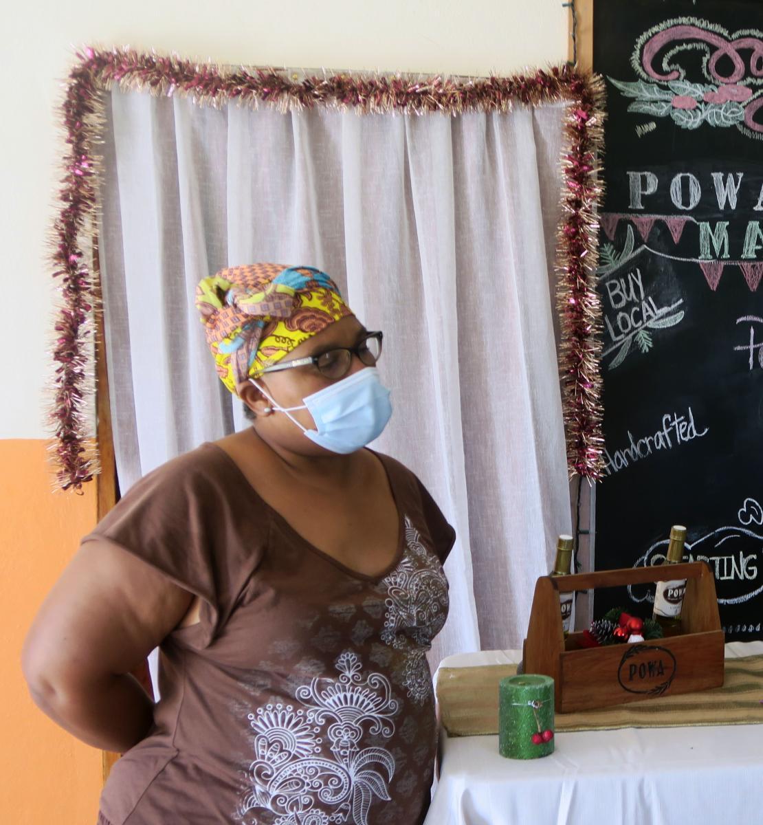 在POWA赞助的集市上,一名戴着口罩的妇女站在她自制的油和肥皂前。