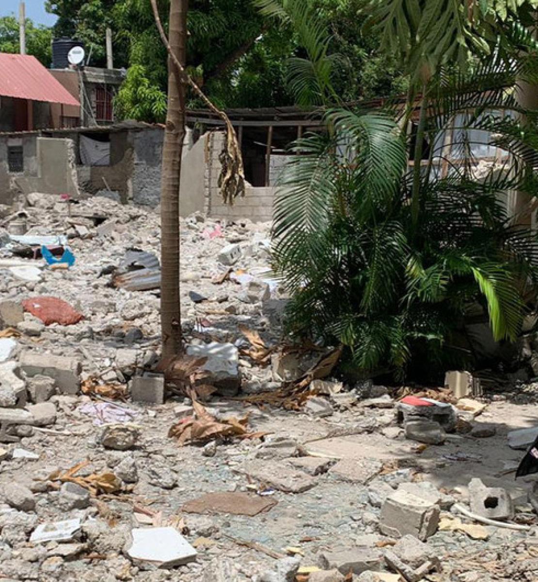 联合国副秘书长阿米娜·穆罕默德站在房屋废墟的右边。